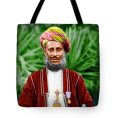 """African Official Tote Bag 18"""" x 18""""  Found this image as a damaged and scratched black and white photograph. Have spent hours repairing the photo and got carried away as I decided that it would look marvelous as colorized image. Spent way too much time on this image but loved my waste of time.  I just loved the pride this man showed in his beautiful costume, red green turban, sword, medallion, grey beard and mustache. Also the contrast between red dress and green foliage in the background."""