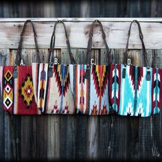 A) Navajo purse with zip closure and rein style straps. Includes mustard yellow, red, black, and white colors with arrow designs.  B) Navajo purse with zip closure and rein style straps. Includes tan, light blue, red, ivory, black, and yellow colors lined with arrow designs. C) Navajo purse with zip closure and rein style straps. Includes grey, yellow, red, black, and ivory designs colors lined with arrow designs. D) Navajo purse with zip closure and rein style straps. Includes turquoise…