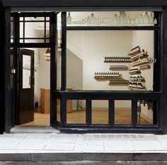 Aesop store {shoreditch, london}. Black window frames, a simple timber floor, freestanding counter and elements that celebrate the old existing space. The product  is framed in the view.