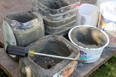 Home made concrete planters! Mix a package of concrete per directions, fill in an old plastic container and stick in a second container to create a void. The next day, carefully pull out the second container and scoop out a drain hole with a screwdriver while it's still not completely set.