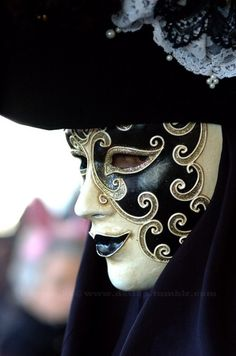 An amazing black and ivory costume and mask with metallic scroll detail