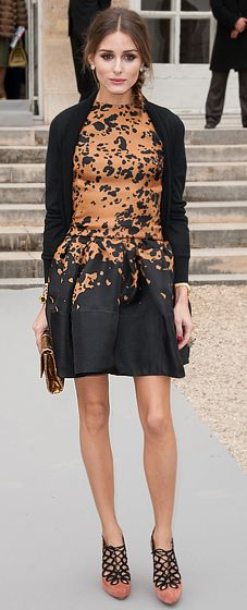 in a printed silk Christian Dior dress and coral suede pumps at the label's Fall 2012 Presentation in Paris.
