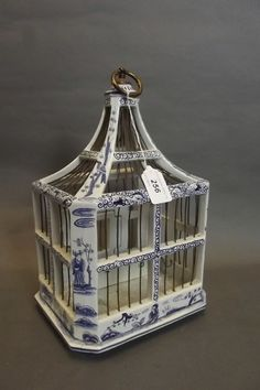 An unusual C19th Dutch Delft blue and white birdcage painted with chinoiserie figures etc, the underside also decorated, 8'' x 6½'', 12'' high