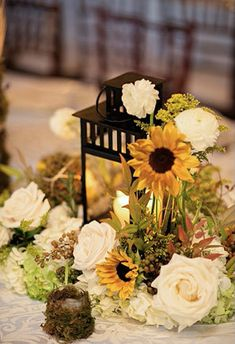 Elegant rustic wedding tablescape with moss covered votives, black lanterns, white roses, and sunflowers.