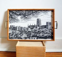 Vintage wood tray collectible 1970s souvenir from England with pen and ink drawing art of Durham Cathedral by Ronald Beavan. Mostly known for his artwork of birds, here Ronald Beavan has done a detailed drawing of the historic Durham Cathedral and its old town surround in the Lake District with trees. This is a very sturdy heavy tray with tongue & groove wood sides and brass handles in very good vintage condition. The image is immaculate and must never have been used to actually serve or…