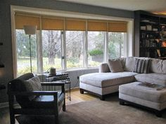Q: I can't figure out a practical, budget-friendly, good looking window treatment solution for the large bow window in our family room. The woven roller shades on the windows right now are ok — and I wouldn't be opposed to keeping them up — but I'd like to add drapes or something to soften them up. I'm not concerned at all about blocking out light, but I would like to have some privacy at night — we are really on display when the sun goes down!… Sent by Melissa