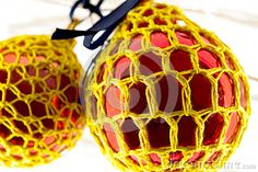 A close up  of  red baubles covered with yellow crotchet