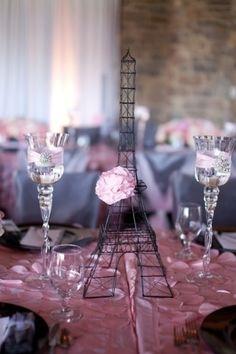 A Torre Eiffel, um dos símbolos da cidade de Paris, tema deste chá de bebê sofisticado, estava por toda parte, ajudando a decorar a festa. Aqui ela aparece como centro de mesa, entre as taças enfeitadas com laços