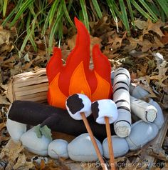 Something similar to this.  I like the logs larger, but I do like the tan (cut) log in the back-left corder. Possibly can make a rock ring out of gray leggings, fiberfill, and rubber bands. This fire sucks.