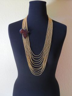 Eleven strand yellow gold seed bead Africa adorned statement necklace.