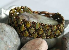 Czech Glass Silky Glass Pearl Bracelet Embellished with O Beads and Toho Seed Beads Czech Silky Diamond Beads ~ 6mm Green Opaque Picasso Czech O Beads ~ Jet Picasso 3mm Round Pearl Beads ~ Chocolate Toho Beads ~ 11/0 Bronze Toho Beads ~ 15/0 Bronze Clasp ~ Antique Copper Circle Toggle Bracelet measures 3/4 in width and 6-1/2 in length including the clasp. Design Courtesy of Desert Star Creations. ¤´¨) ¸.•´¸.•*´¨) ¸.•*¨) Thank you for visiting!! (¸.•´ (¸.•`¤ All items at Reggies Creation...