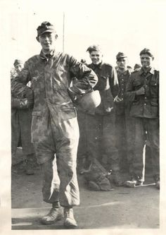 1944- Captured German paratrooper steps forward from smiling fellow prisoners at Anzio and poses for photographer.