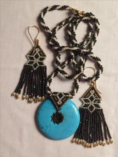 A turquoise magnesite donut and beadwork pendant with matching earrings fashioned from 15• Charlottes and 15• 24kt gold beads bohobeads@yahoo.com