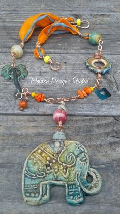 Inspired by Hano the elephant for the bnb challenge, elephant focal is polymer clay by Staci Louise Originals, sari silk ceramic disc by Marsha Neal Studios, brass patina stamping, ceramic beads by Gaea Canody, and copper wirework
