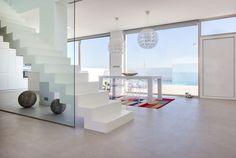Chiralt Arquitectos I Escalera de microcemento en salón de vivienda moderna.