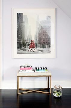 Ottoman styled with books under framed fashion photograph.