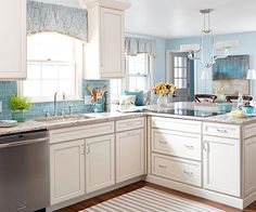 White cabinets make a design splash thanks to off-white finishes and glazed panels and recesses. The patina lends the kitchen a traditional, timeworn appearance, matched by mottled countertops and an always-classic blue glass subway tile backsplash.