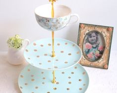 This lovely 3 tier cake stand was made using a combination of 2 plates and one small jar. The base plate is solid blue, the middle tier is white with hand painted blue polka dots. The top tier small jar is white with lovely pink roses and blue polka dots.  The teapot is not included.  You can set up the fittings for single, double, triple tiers.  Perfect tiered cake stand for a celebration such a wedding, bridal shower, baby shower or tea party.  Base plate measure: 11 across The middle…