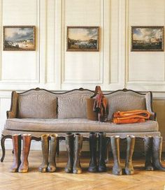 English ticking stripe sofa, riding boots, landscape art, and wall paneling.... It sure evokes the feelings of an old English Manor....