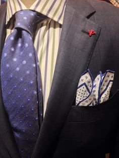 Isaia's signature coral seen pinned to a suit lapel and woven into a pocket square.
