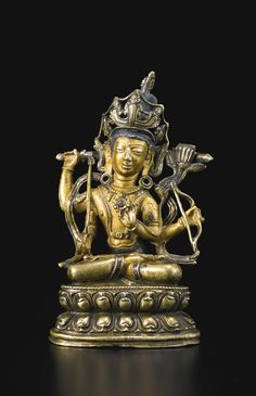 A COPPER ALLOY FIGURE DEPICTING MANJUSHRI TIBET, 14TH CENTURY the four-armed deity with upper body and soles of feet cold-gilt, wearing a high five-pronged crown, the primary arms holding a sword and a lotus with Buddhist text, the secondary arms holding a bow and arrow, the hem of the dhoti inlaid with copper Height 6 ¼ in. (15.9 cm)