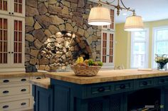 attractive brown stone wall ideas for charming kitchen with dark blue wooden kitchen island and white kitchen cabinet with fancy chandelier and decors