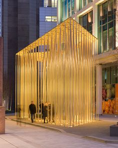 Regents Place Pavilion  The Pavilion is created by a field of steel rods supporting a thin plate canopy 8M above the streetscape.  By night the visual transparency of the structure is reinforced by up-lighting to the clusters of rods - the pavilion appears to hold the warm golden light within its structure.