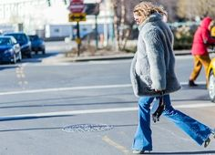 Olivia Palermo wears a gray fur coat, flare jeans, pumps, and a circle bag