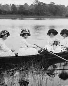 Edwardian ladies rowing in summer whites and elaborate hats, circa 1909.