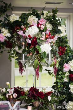 Wedding decor with deep wine burgundy accent - perfect for a fall or winter wedding!  This overflowing arrangement shows us how dark florals are done! | Photography By: Pear Studios Inc. | WedLuxe Magazine