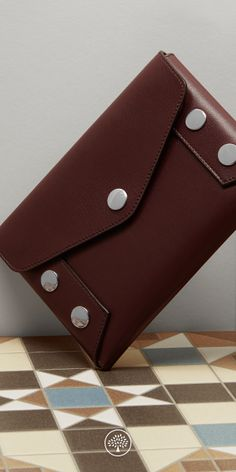 Shop the Envelope Pouch in Oxblood Smooth Calf at Mulberry.com. The Envelope Pouch can be carried as a clutch for smaller essentials, or used as a larger wallet inside a bag. Continuing the theme of the season, the pouch is decorated with Johnny Coca's signature press studs.