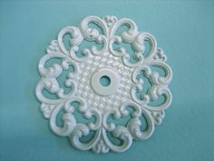 Dollhouse Miniature Large Ceiling Medallion  I have a stack of these former a dresser.  They started as drawer-pull, face plates which I have painted either white or gold.  Recently I have found a way to make extra castings so that I never run out!  They're GREAT :D