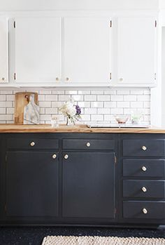 Hardware - Butcher block countertops atop dark-painted cabinets with white cabinetry above.
