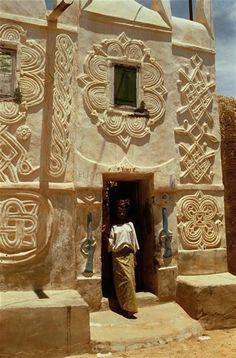 Vrouw voor de deur van een Hausa-huis met traditionele decoraties in Zinder, Niger (foto: Michel Renaudeau).