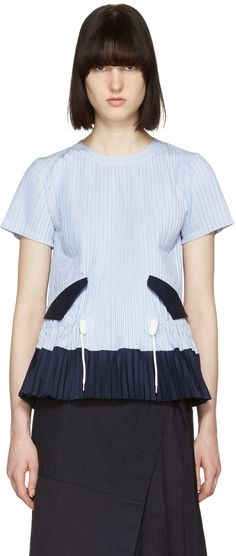 Short sleeve woven cotton blouse featuring pinstripe pattern in blue and white. Pleating throughout. Crewneck collar. Flap pockets in navy and drawstring in white at waist. Gabardine panel in navy at hem. Extended keyhole closure with hook-eye fastening at back. Silver-tone hardware. Tonal stitching.