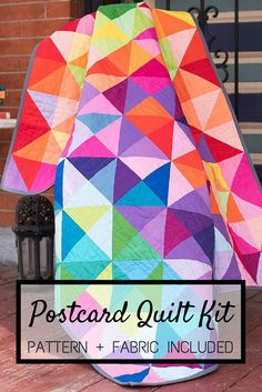 """Believe it or not, this breathtaking quilt was inspired by a few colorful postcards! Your Postcards from Sweden Quilt Kit includes a pattern and Robert Kaufman Kona Cotton, to sew this sensational 48"""" x 60"""" quilt top. Featuring an easy-to-construct, half-square triangle design and all your favorite hues, this kit is simply irresistible!"""