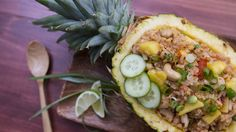 Recipe with video instructions: A sweet tropical infusion into this stir fry classic. Ingredients: 1 ripe pineapple, 3 cups day old cooked jasmine rice, ½ lb boneless skinless chicken thighs, small cubes, 2 eggs, whisked, ¼ cup scallions, thinly sliced, 1 tbsp garlic, minced, ½ cup tomato, sliced into thin wedges, 2 chili peppers, chopped, ¼ cup cashews, 1 lime, Sugar, Black pepper, Thai soy sauce, Fish sauce, Sliced cucumber for garnish, Oil for pan
