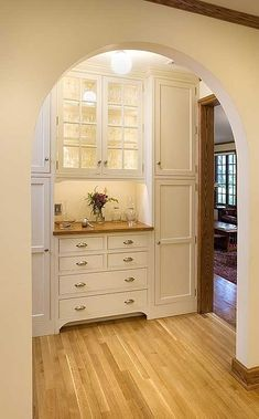 [Just lovely. I like the symmetry, the combination of cream and wood, the pretty glass doors, and the good lighting. The archway is beautiful, and I like the way it frames the cabinetry. It makes a wonderful vignette.]Ideoita