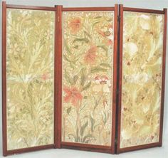 Folding screen designed by John Henry Dearle, c 1885-90. Light mahogany with three different embroidered panels, the first with five poppies, some showing their stamens, and with buds, together with two types of smaller flower, in shades of coral with green and ivory on a beige pink ground, the second with Parrot Tulip design with six tulips in similar colouring but with some stronger coral and crimson, two types of small flowers on a pinky beige ground, the third with Large Horned Poppy…