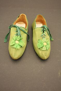 Green cloth shoes with green silk cockades with stamped brass centers, and green silk binding and laces, mid-19th C.