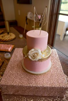 One large white rose contrasts marvelously against this pink-and-gold wedding cake.