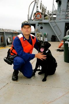 Beautiful photo of Petty Officer 1st Class Joseph Tokarsky, a maritime law enforcement specialist with the Maritime Safety and Security Team San Francisco, poses with Sirius, a explosive detection dog, on the moored Jeremiah O'Brien at Pier 45 in San Francisco. The training prepares the dogs for boarding larger ships at sea. U.S. Coast Guard photo by Petty Officer 2nd Class Pamela J. Boehland.