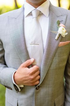 Cream and peach flower boutonniere for groom in light grey suit and tie with peach and white polka dot pocket square for summer wedding