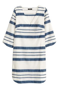 White/striped. Striped dress in woven cotton fabric. 3/4-length sleeves, V-neck, and gently rounded hem. Unlined.