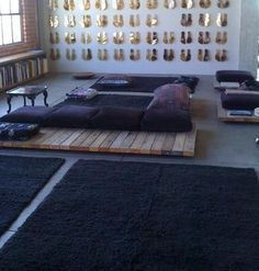 i like all the floor cushions a mural of golden traced feet covers a wall blue couches living rooms minimalist