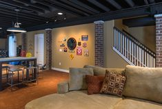 A warm, comfortable basement family room with an industrial flair with rough, brick. Exposed ceiling was sprayed black. Oversized shop pendant light.