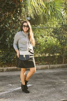 Faux leather skirt paired with booties makes for a great mild winter weather look! I kind of love the idea of dressing up a sweatshirt. A once casual and comfy sweatshirt becomes part of a more dressed up ensemble!