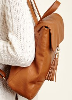 A vegan leather backpack with straps and two front tassels. Includes adjustable shoulder straps.