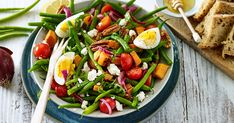 500 g sperziebonen; 2 eieren; 1 zoete aardappel; 2 rode uien; 1 citroen; 2 tl honing; 250 g cherrytomaten; 100 g feta; 100 g pecannoten; 3 el olijfolie; zout; peper