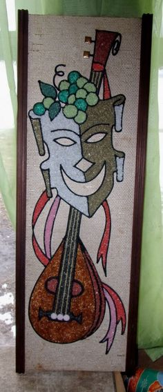 """This is a 1960s  vintage mid century modern pebble or gravel art.  It is a comedy mask with a lute.  It is 24"""" x 8 1/2"""" in its wooden frame."""